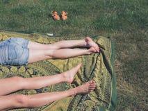 Lle gambe di due giovani donne fuori su erba Fotografia Stock