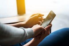 Lle mani di due donne parlano insieme mentre sguardo allo smartphone ed al Li Fotografia Stock