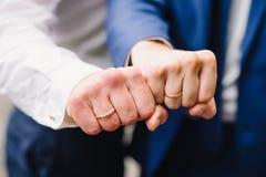 Lle mani di due uomini con gli anelli di oro di nozze Immagini Stock