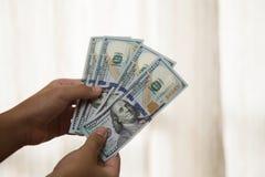 Lle note della tenuta della mano di cento dollari americani immagini stock