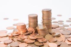 Lle pile di metallo conia ai precedenti bianchi con altre monete intorno immagine stock libera da diritti