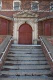 Lle scala incrinate conducono ad una porta rossa Fotografia Stock
