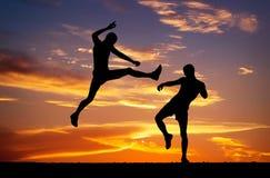 Lle siluette di due combattenti sul fondo ardente di tramonto Fotografia Stock