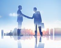 Lle siluette di due uomini d'affari che hanno una stretta di mano Fotografie Stock