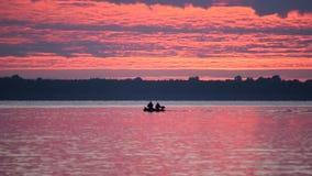Lle siluette di due uomini in una barca all'alba su acqua video d archivio