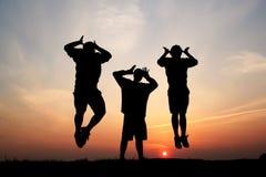 Lle siluette di un salto dei tre uomini Immagini Stock Libere da Diritti