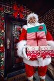 Llega Santa Claus y el regalo de la Navidad de las porciones que lleva Foto de archivo