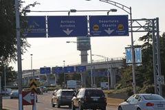 Llegadas y señal de tráfico de las salidas en aeropuerto de YVR Fotografía de archivo