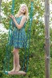 Llene el retrato de la longitud de la muchacha rubia en los sundress de seda en el oscilación hecho a mano fotos de archivo