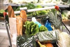 Lleno de carretilla que hace compras de los productos en supermercado imagen de archivo