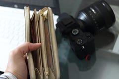 Lleno de mano de la cartera del dinero en fondo de la cámara de la falta de definición fotografía de archivo