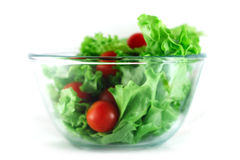 Llettuce and tomatoes salad. Lettuce and cherry tomatoes salad in transparent bowl isolated on white Royalty Free Stock Photo
