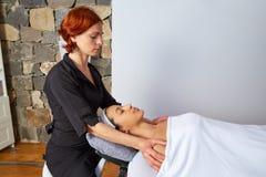 Lleva a hombros a la mujer del fisioterapeuta del masaje del cuello Imagenes de archivo