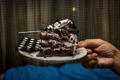 Llevando a cabo una rebanada de torta de cumpleaños del chocolate - en una placa fotografía de archivo libre de regalías