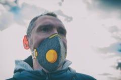 Llevando un anticontaminación real, contra la niebla y los virus la mascarilla imagen de archivo