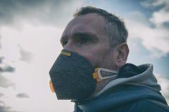 Llevando un anticontaminación real, contra la niebla y los virus la mascarilla fotografía de archivo libre de regalías