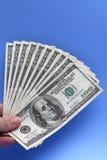 Llevar a cabo cientos billetes de dólar Imagen de archivo libre de regalías