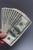 Llevar a cabo cientos billetes de dólar Imágenes de archivo libres de regalías