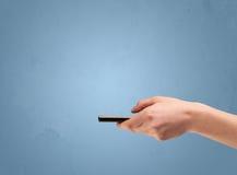 Llevar a cabo el dispositivo del teléfono del perfil Imagen de archivo