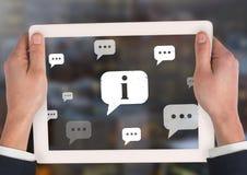 Llevar a cabo iconos de la tableta y de las burbujas de la información y de la charla en ciudad Foto de archivo libre de regalías