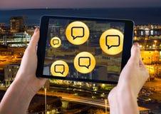 Llevar a cabo la tableta y burbujas de la charla sobre ciudad de la noche Imagenes de archivo