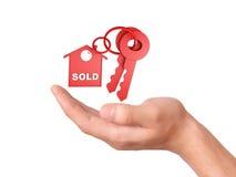 Llevar a cabo llaves de la casa concepto vendido Imagen de archivo libre de regalías