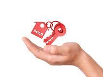 Llevar a cabo llaves de la casa concepto vendido Fotos de archivo libres de regalías