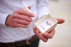 Llevar a cabo los anillos de bodas en una caja Foto de archivo