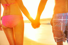 Llevar a cabo pares de las manos en traje de baño en la playa Imagen de archivo libre de regalías