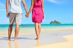 Llevar a cabo pares románticos de los recienes casados de las manos en la playa Imagenes de archivo