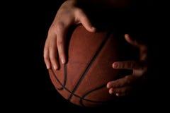 Llevar a cabo un baloncesto en negro Foto de archivo