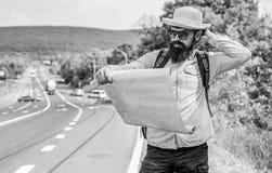 Lleve el buen mapa Miradas turísticas del backpacker en el mapa que elige el destino del viaje en el camino Allow reconoce bastan imagenes de archivo