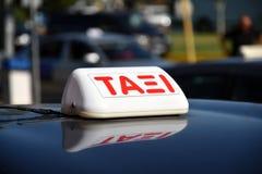 Lleve en taxi firman adentro la lengua griega en el tejado brillante de un coche imágenes de archivo libres de regalías