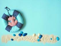 Llifeline, escudos do mar e areia branca no fundo azul fotos de stock royalty free