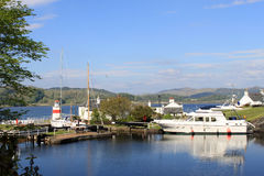 Llighthouse, boat and canal basin Crinan Canal. View of the Canal Basin at the West end of the Crinan Canal, Argyll and Bute, Scotland showing a moored boat and Royalty Free Stock Image