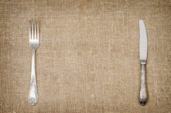 Llinen background with old silver fork and knife. Rustic linen background with vintage silver fork and knife Royalty Free Stock Photography