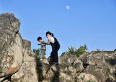 Llittle男孩设法上升与岩石的妈妈 库存图片