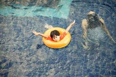 Llittle boy in life ring having fun on swimming pool stock photography