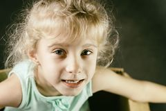 The little blonde smiles inside a cardboard box. dark background. stock images