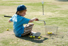 Llittle boy on a golf field Stock Photo