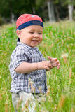 Llittle boy on green summer meadow Royalty Free Stock Image