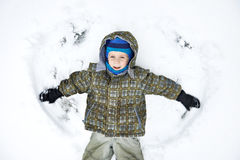Llittle boy lies on snow and playing. Llittle boy lies on snow and waving his arms Royalty Free Stock Image