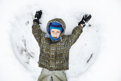 Llittle boy lies on snow and playing. Llittle boy lies on snow and waving his arms Royalty Free Stock Photo