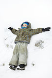 Llittle boy lies on snow and playing. Llittle boy lies on snow and waving his arms Royalty Free Stock Photos