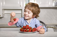 Llittle boy with strawberry Stock Images