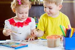 Llittle brother and sister painting at home Stock Photo