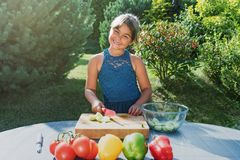 Llittle girl is cooking salad from fresh vegetables. Smiling little girl is cooking salad from fresh vegetables outdoors. Girl is looking at the camera Royalty Free Stock Photo