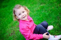 Llittle girl with curly hair on green grass Royalty Free Stock Photography