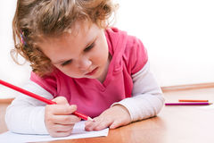 Llittle girl drawing around her hand royalty free stock images