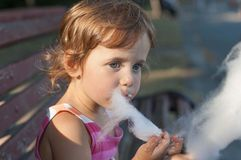 Llittle girl eating cotton candy in the park Stock Photos